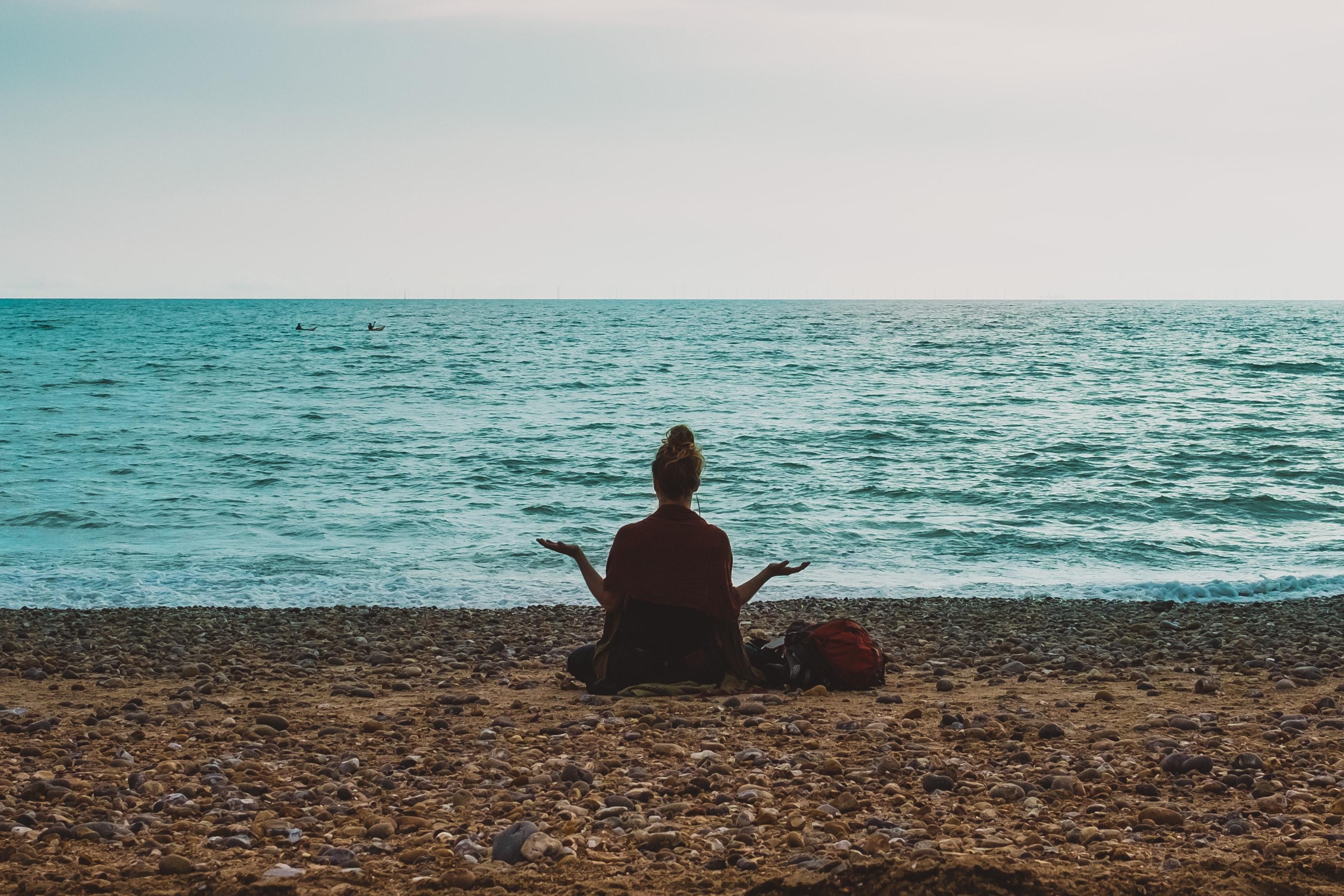 2021 Woman meditating on rock beach- processingly-2pUP1Ts1bmo-unsplash